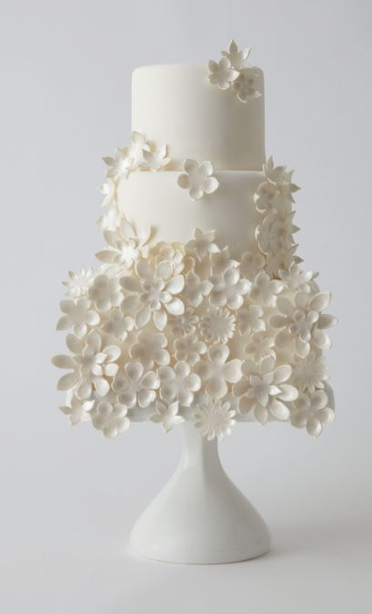 Things I like about this great cake: The bottom tier is covered completely in flowers, even like they're falling off the cake, as well as scatterings on the top two tiers.