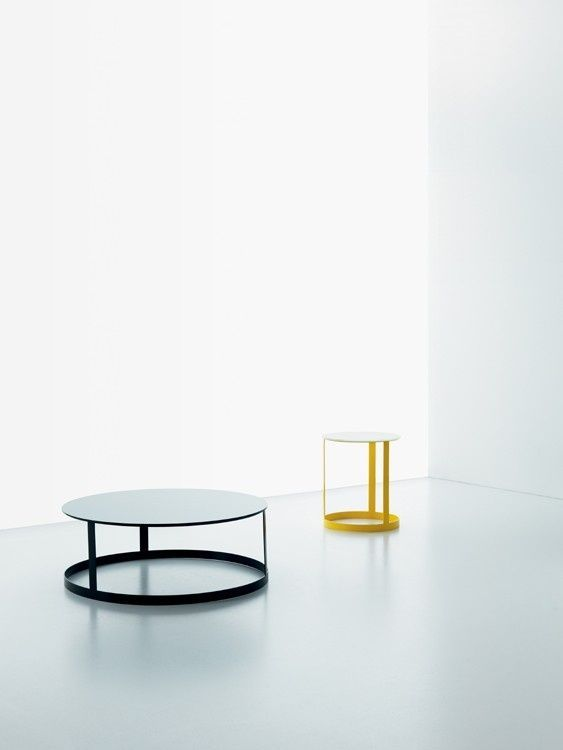 Design:  Giopato e coombes. Tavolino da salotto, comodino con piani rotondi in vetro o legno e basamento in metallo.