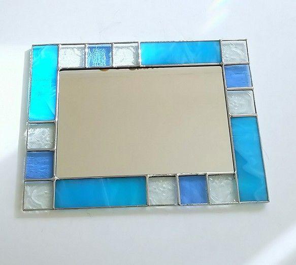 受注制作品です。ご購入手続き後にお作りさせて頂きます。3日から1週間程お待ち頂きますのでご了承お願いいたします。ステンドグラスの鏡です。アクアブルーとクリアと白いガラスとライトブルーを組み合わせたシンプルな、すっきりとした鏡です。アクアブルーのガラスは濃淡の流れの有るガラスです。フローラガラスのクリアガラスと白いガラスとライトブルーを組み合わせて、すっきりと爽快なイメージの鏡になりました。玄関、キッチン、お手洗いに、お気に入りの場所に…。壁掛けは縦横に出来ます。卓上は、イーゼルをご使用頂き縦横お好きな方向で飾って頂けます。壁に寄りかかるように飾る時には滑り止めをひいて、念のため、画びょう等で前から見えないように壁に留めて頂くと地震などによる破損予防になります。サイズ 縦20cm 横15cm(鏡 縦15cm横10cm)インテリアハンドメイド2017#ホワイトデー#プレゼント#贈り物#新築祝い#模様替え#ターコイズブルー#鏡#北欧#クリスマス#敬老の日