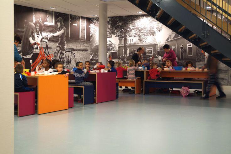 Interieurontwerp wijkhuis Brede school Westwijzer. Gang wordt lunchruimte voor de kinderen met kleurrijke banken en tafels.