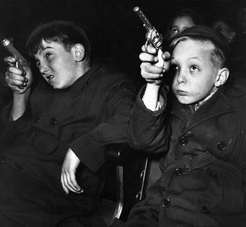 Boys with toy guns at a children's movie session, United Kingdom, 1954, photograph by Paul Kaye.