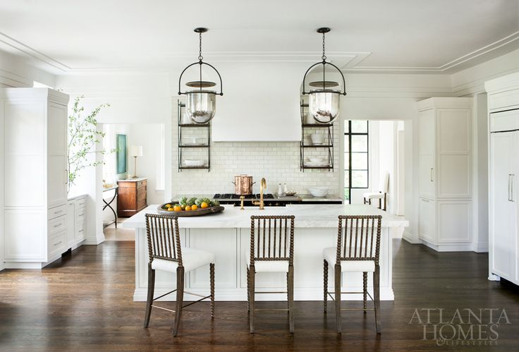 """""""We wanted everything to look like it might have been original,"""" says designer Nancy Duffey, who selected classic bell-jar lanterns and a brass faucet for the kitchen, both of which are in keeping with the age of the house. Platter, B.D. Jeffries. Chairs, Holland & Company. —"""