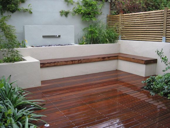Rendered tall end boundary wall, with built in planting and seating and lower wooden horizontal fencing between properties.