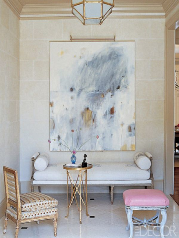 Beautiful, oversized artwork placed over a white settee, gold accents and marble floors | Elle Decor