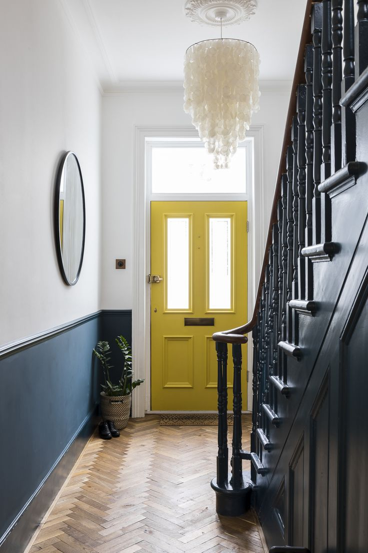 Interior Design by Imperfect Interiors at this Victorian Villa in London. A palette of contemporary Farrow & Ball paint colours mixed with traditional period details- Hague Blue spindles, staircase and white walls, a sunshine yellow front door, a large metal framed round mirror, Capiz shell chandelier and herringbone parquet make this entrance contemporary but still grand. Photo by Chris Snook