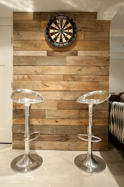 Dart board... Love the rustic cladding behind it!