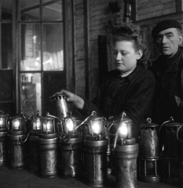 """""""Mine de Lens en 1945"""" © Photo by Doisneau Scène à la lampisterie avant la descente, les lampes électriques sont connectées, des lampes de sureté à flamme de type Wolf sont également préparées. Les premières sont destinées aux ouvriers mineurs, les secondes qui ne servaient quasiment plus qu'à la détection des gaz sont elles destinées, à la maîtrise, aux gaziers et boutefeux ; autant de métiers liés à la mesure de la teneur en méthane ( grisou )."""