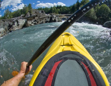 Stock Photo : Whitewater kayaker paddling rapids in river