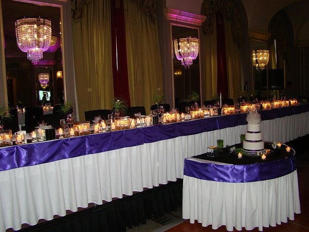 Dramatic Tablescape   The architectural elements of the room were accented with purple uplighting. In order for the head table to have impact against this, we went for a heavily laden table with candles in various vessels. This added interest to the table as well as did a great job of illuminating the gals and guys seated there.This design and decor done by grandbeginningsdecor