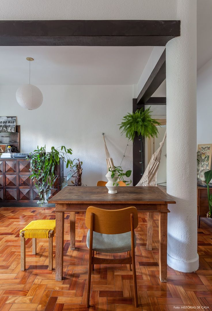 Sala de jantar tem mesa de madeira de demolição e ao fundo armário antigo de madeira.