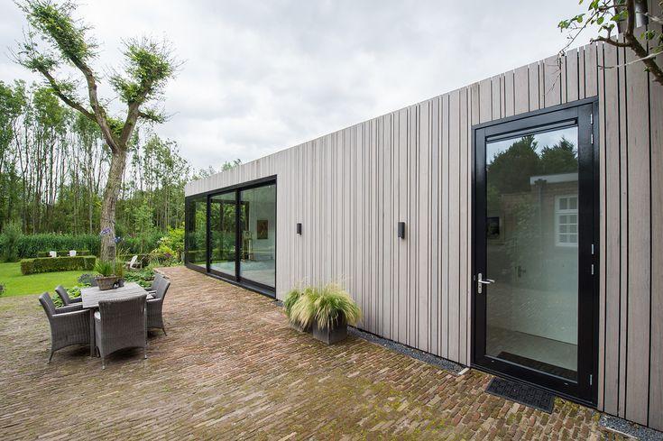 Vanuit de woning kijk je door de grote glazen deuren richting tuin achter het atelier. Dit geeft meer lucht en breedte aan de tuin die nu overblijft direct achter de woning en naast het atelier. Dit was anders te massief geworden.