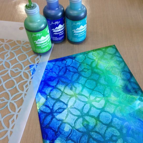 By Richele Christensen. Squirt 3 colors of alcohol inks onto a non-stick craft mat (colors used: Botanical, Indigo, Mermaid). Add Blending Solution to the inks. Swipe glossy cardstock through the inks. Swipe a second & third piece through the inks also if there is enough ink left on the mat. Secure a stencil over one inked sheet. Apply Blending Solution to a blending tool & pounce over the entire piece until you like the look.