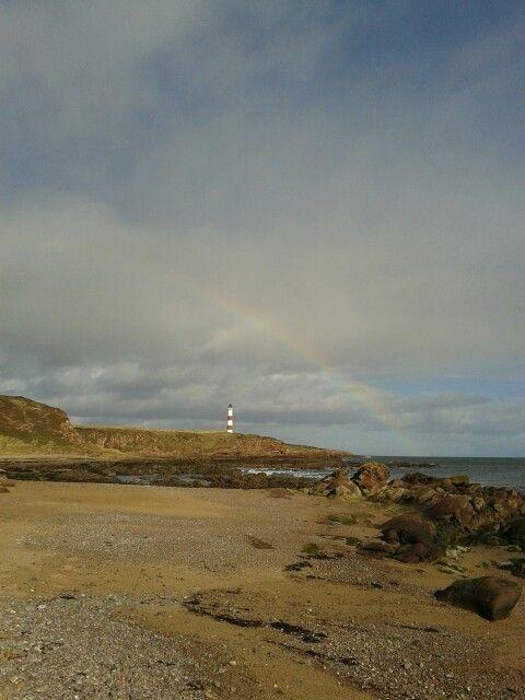 Coastal beach lighthouse rainbow