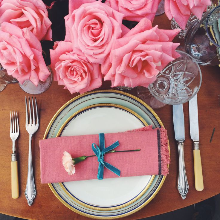 Romantic scenery dinner. Pink roses bouquet, vintage cutlery. Romantic tabletop. Vintage, Bavaria porcelain plates and cristal glasses. Outdoor dinner.