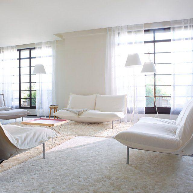 """Un canapé blanc """"Calin"""" style banquette, dans un salon tout blanc avec de jolis voilages, de la moquette blanche et des abat-jour blancs. Canapé design Pascal Mourgue, Cinna"""