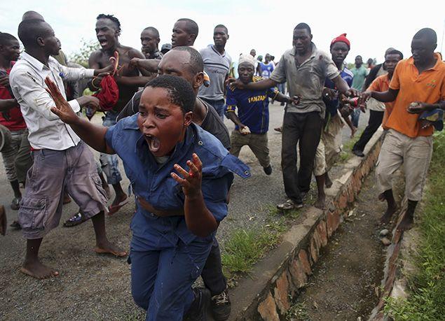 12 mai 2015 - Des manifestants attaquent une policière accusée d'avoir tiré sur un manifestant dans un quartier de Bujumbura, au Burundi. Les manifestants opposés à la décision du président de briguer un troisième mandat ont pourchassé, battu et lapidé la femme, qui a ensuite été restituée à la police. REUTERS / Goran Tomasevic