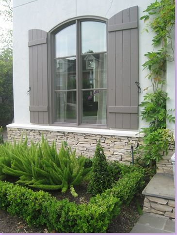 Sally Wheat, boxwoods, foxtail fern, gray shutters, stone