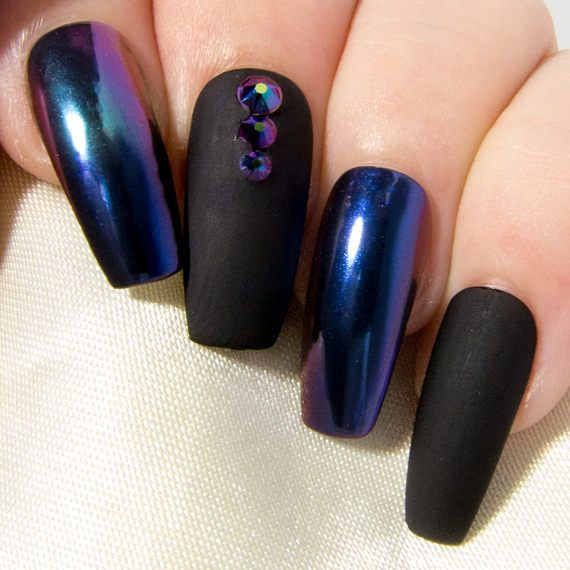 If youre loving the chrome nail trend, but find that glitzy silvers and prissy-pinks are really not your thing, then these matte and chrome false nails were made just for you! Starring a deep, inky matte black, an enchanting green and navy chrome ombre, and blue-purple-green iridescent Swarovski® crystals, this mysterious mani is sure to appease the very darkest depths of your soul. Coated with two layers of gel top coat for extra durability and a glassy-smooth surface, these false nails…
