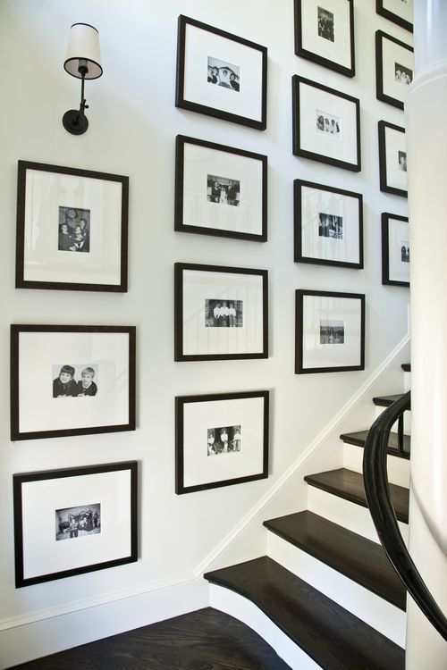 A chic and neat stairway gallery wall with black frames and large white mats black and white photos