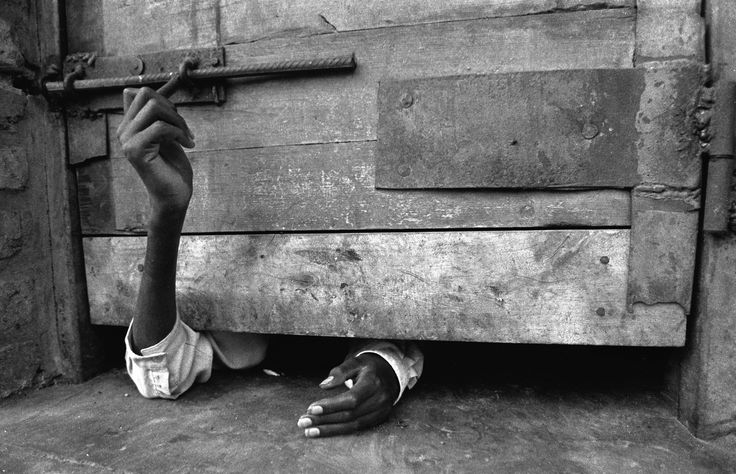 Photograph by David Guttenfelder~~~A man tries to unlock a cell door at a hospital in Kigali, Rwanda in 1994. As the genocide spread across the country, doctors and staff of the main psychological hospital in Kigali fled or were killed leaving the patients to care for themselves.