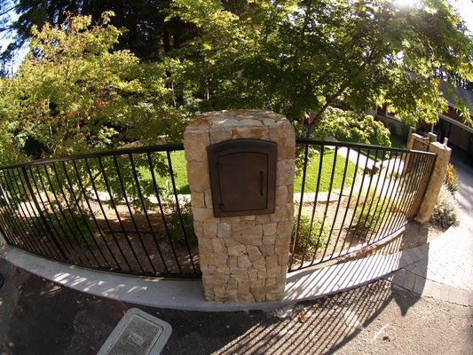 landscaping mail box and fence | Metal mailbox built-in in one of the stone pillars holding the black ...