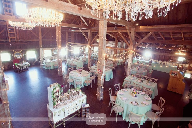 Here's a great interior shot of the inside of the rustic timber frame barn at Bishop Farm used for the wedding reception. Love all of the chandeliers and rough-sewn wood!  Located in northern NH, this is the perfect outdoor wedding venue in New England!  #dreamlovephotography #bishopfarmnh #barnweddingnh