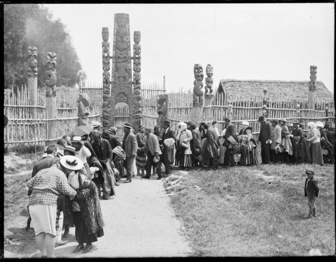 A line of Maori men and women shaking hands and touching noses (hongi), in front of the carved gateway of the pa. The gateway is flanked with tawai-sapling fences. Photograph taken between 1906 and 1907, by Leslie Hinge.