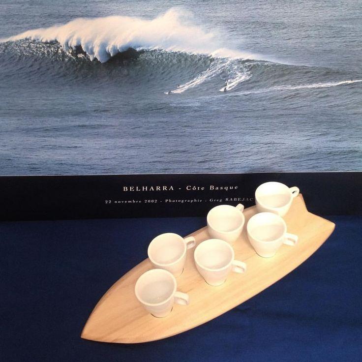 """Ce set en forme de planche de surf a été réalisé en paulownia, un bois flexible très léger qui lui permet de flotter sur l'eau et avec lequel sont notamment fabriquées les """"alaias"""", ces planches de surf en bois massif et sans dérive, inspirée des premières planches fabriquées dans le Pacifique.  Elles sont aujourd'hui très prisées des surfeurs à la recherche d'un retour aux sources de cette discipline telle que la pratiquaient à l'origine les Polynésiens"""