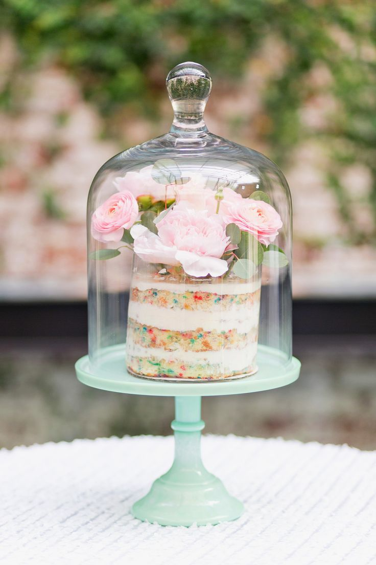 Serve each bridal shower guest a personal naked confetti cake in a dainty cloche—fresh florals add a botanical element.