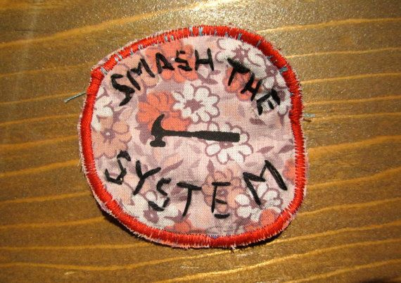 One of a kind handmade Smash the System Badge This badge was hand printed on recycled materials with fabric ink and heat set.  The text was hand embroidered and the boarder machine sewn. The patch itself is printed on cotton and then secured to thick upholstery fabric for strength on the back.  *This item was produced in a shop that is home to a little kitty.  Please be leery or send me a message about this if you have sever allergies.*