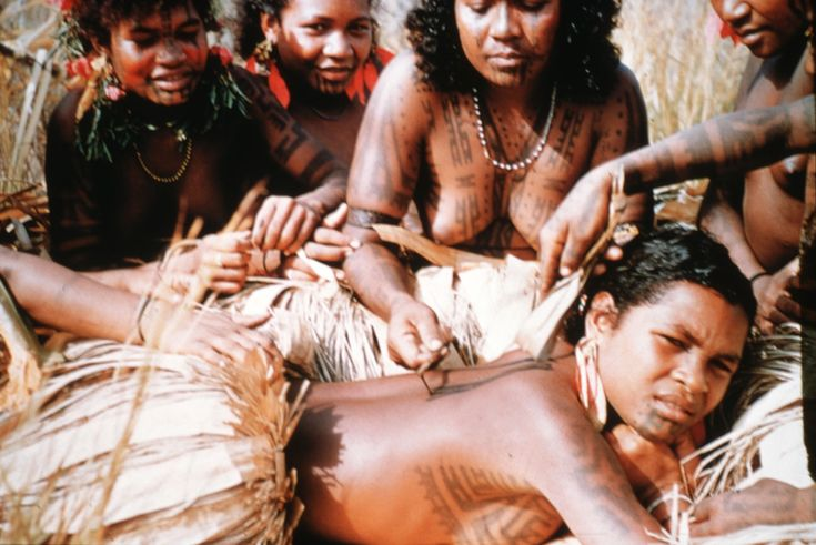 1958 image of a Motuan female tattooing the back of a young woman in Manu Manu, Papua New Guinea. Photo by Percy Cochrane, 1907-1980. Part of the University of Wollongong Archives. #VanishingTattoo #VintageTattoos #TattooHistory
