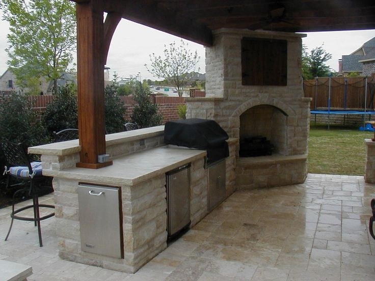Outside kitchen with grill and stone corner fireplace under the roof