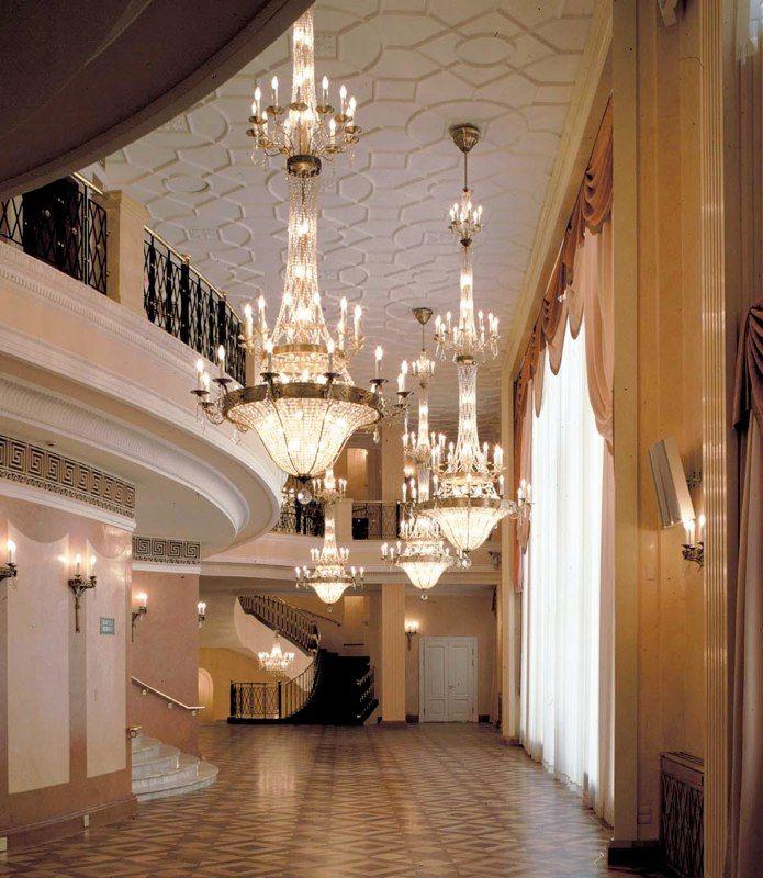 Изящные люстры в вестибюле театра http://www.lustra-market.ru/blog/izyashhnye-lyustry-v-vestibyule-otelya/  Прекрасные люстры в торжественном дворцовом стиле делают уютнее вестибюль театра с его лестничными развязками. Двойной ряд рожков-свечек освещает и верхние галереи, и нижний зал. Небольшие бра на стенах повторяют основной мотив прекрасных люстр.