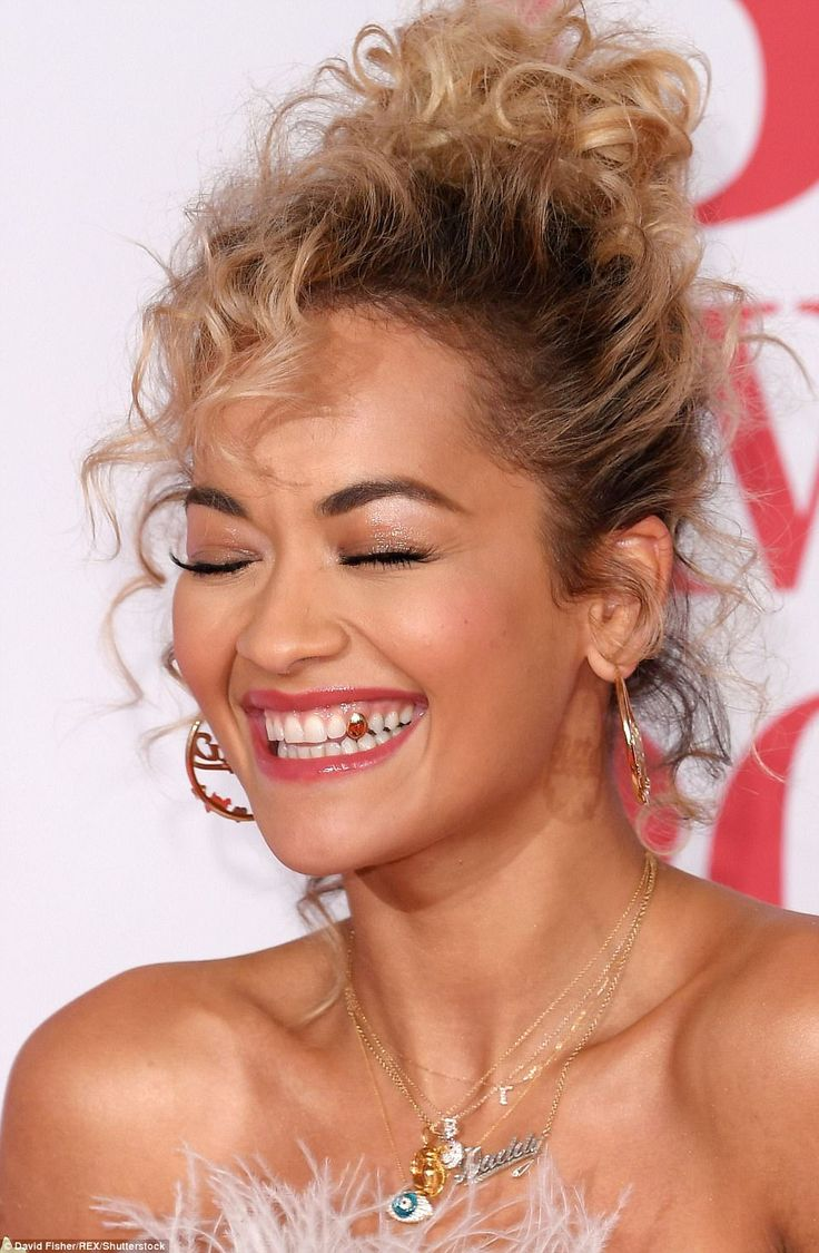 Going for gold: Rita showed off her gold tooth as she giggled on the red carpet...
