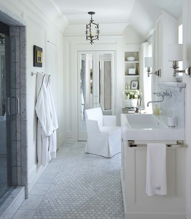 Stunning bathroom with marble tiled walk-in shower with glass door opposite an ivory sink vanity mounted with a trough sink paired with a wall mount faucet framed by a marble backsplash with window above lit by polished nickel wall sconces.