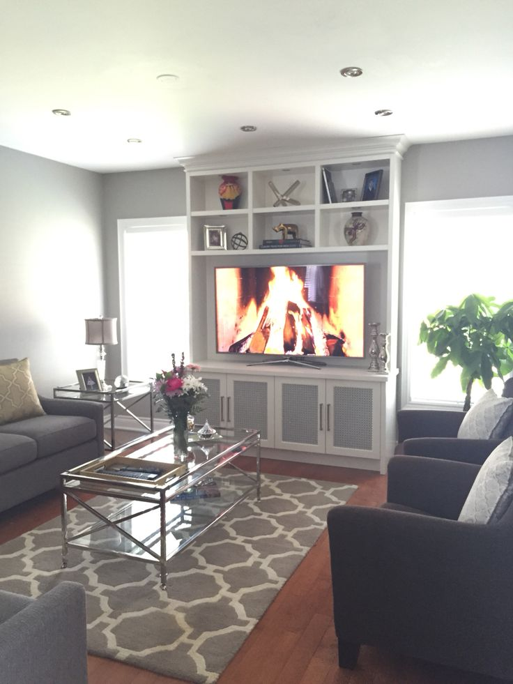 Elegant, contemporary wall unit /built in finish in Benjamin Moore CC-40  with upper cubbies for display purposes and door frames with painted meshin the same finish by Watchtower Interiors Inc. In Toronto