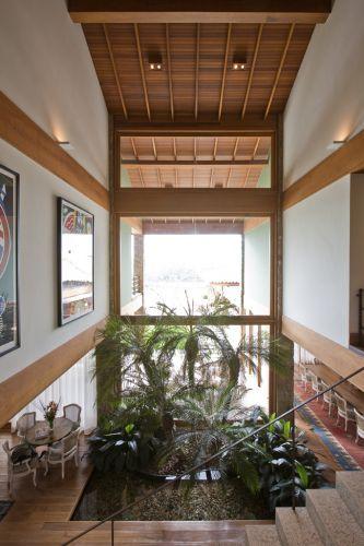Vista do hall central a partir da escada. O pano de vidro ilumina o jardim interno e dá leveza ao espaço que tem, à direita, a sala de jantar e, à esquerda, os ambientes de estar. Casa de campo em Bragança Paulista (SP), projetada por Erick Figueira, com projeto de paisagismo de Maria João D'Orey