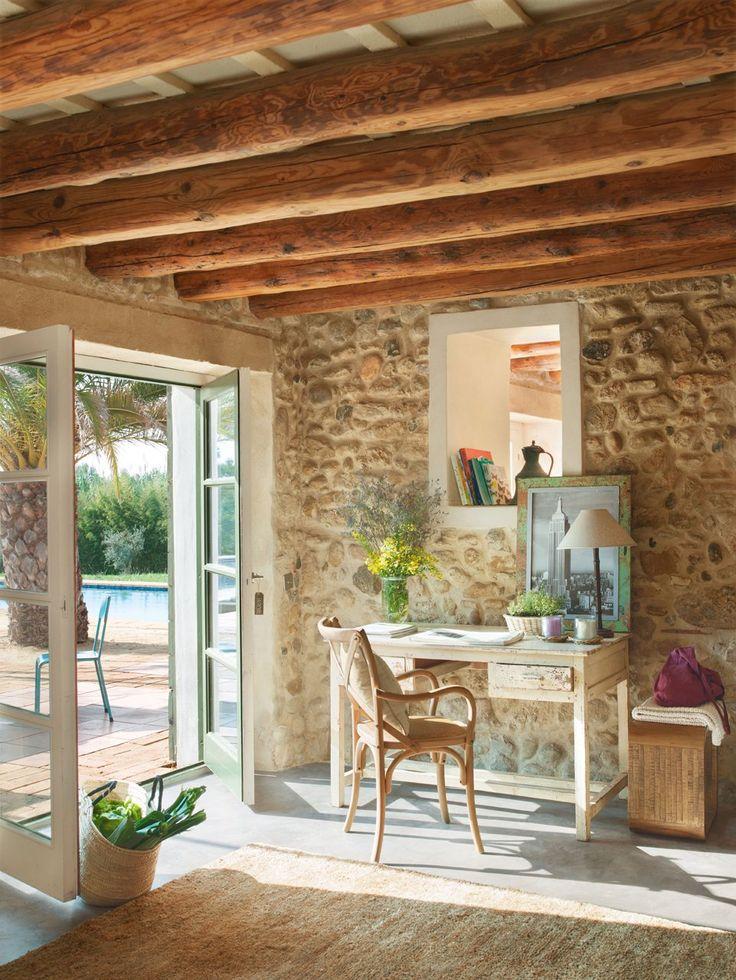 Hall de entrada. Carpintería blanca o madera cepillada, pared piedra vista, alfombra yute. Una casa rústica llena de vitalidad · ElMueble.com · Casas