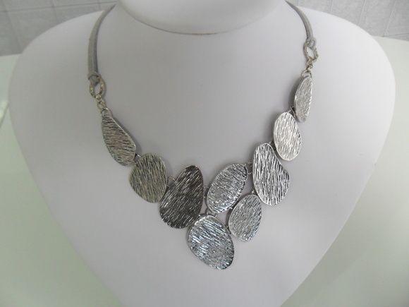 Maxi colar confeccionado com peças em metal níquel escovado.  Acabamento com fios duplo de couro ecológico na cor prata.  Possuem corrente alongado.    (PRODUTO A PRONTA ENTREGA) R$ 33,00