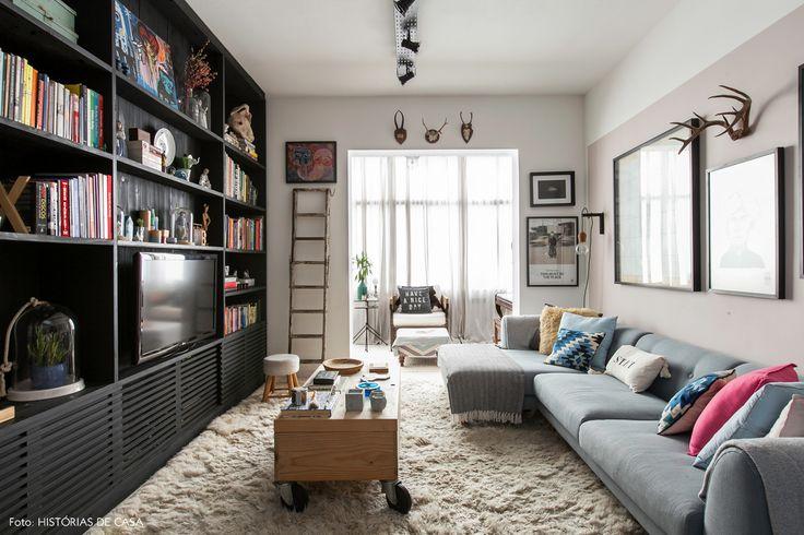 Sala de estar tem estante de marcenaria na cor preta, mesa de centro de pinus e  sofá azul claro com almofadas estampadas.