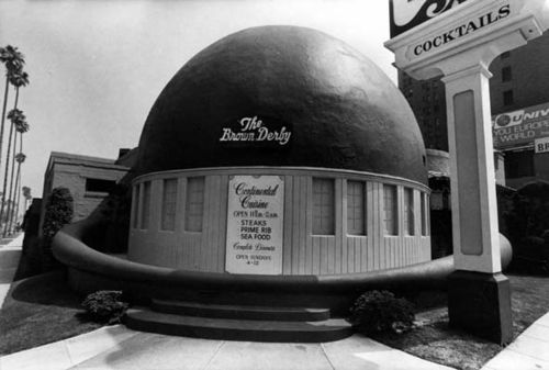 """There were four Brown Derby restaurants: Beverly Hills, Los Feliz, Wilshire and Alexandria, and the most famous on Vine Street in Hollywood. This shows the exterior of the famous """"derby-shaped"""" at the Wilshire Boulevard location in Los Angeles. The derby without its brim is now the roof of a restaurant in the back corner of the minimall that now stands in the same location. (1957)"""