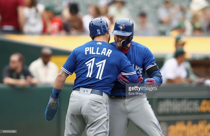 Josh Donaldson #20 of the Toronto Blue Jays is congratulated by Kevin Pillar #11 after he hit a two-run home run in the tenth inning against the Oakland Athletics at Oakland Alameda Coliseum on June 7, 2017 in Oakland, California.