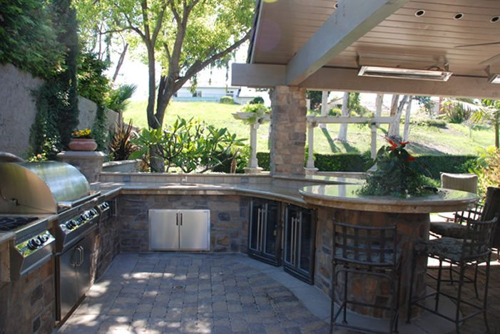 Large outdoor kitchen with curved counter and bar stools