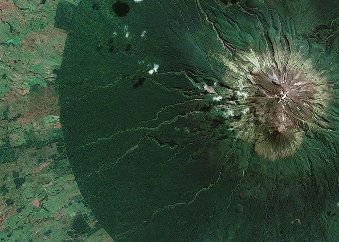 Parque Nacional Egmont em North Island, na Nova Zelândia, é visto através de satélite. A fronteira entre as áreas protegidas e não protegidas pode ser vista de forma clara na imagem: a parte densamente florestada é a área verde escura, e a paisagem agrícola aparece na tonalidade mais clara. A montanha no centro do parque nacional tem dois nomes: Monte Egmont e Monte Taranaki. Taranaki é o nome original dado pelo povo indígena Maori, enquanto o nome Egmont foi dado pelo explorador britânico…