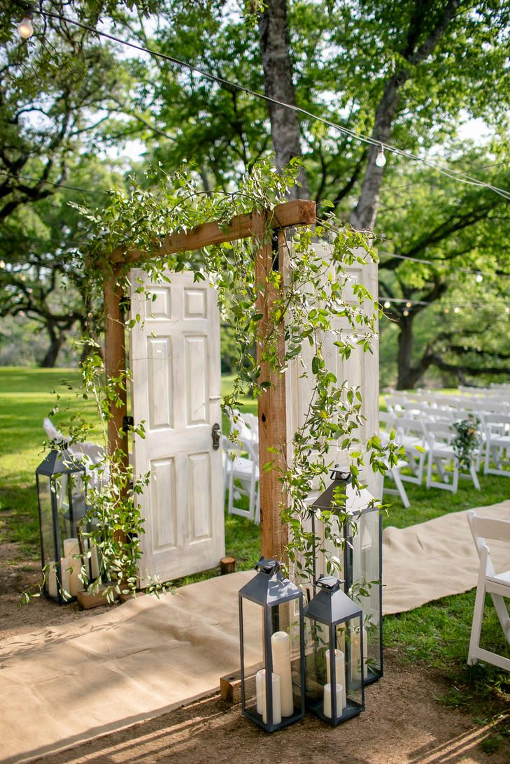 Unique Ceremony Aisle Decor With Open Doors, Lanterns and Greenery | Photo: Nichols Photographers |