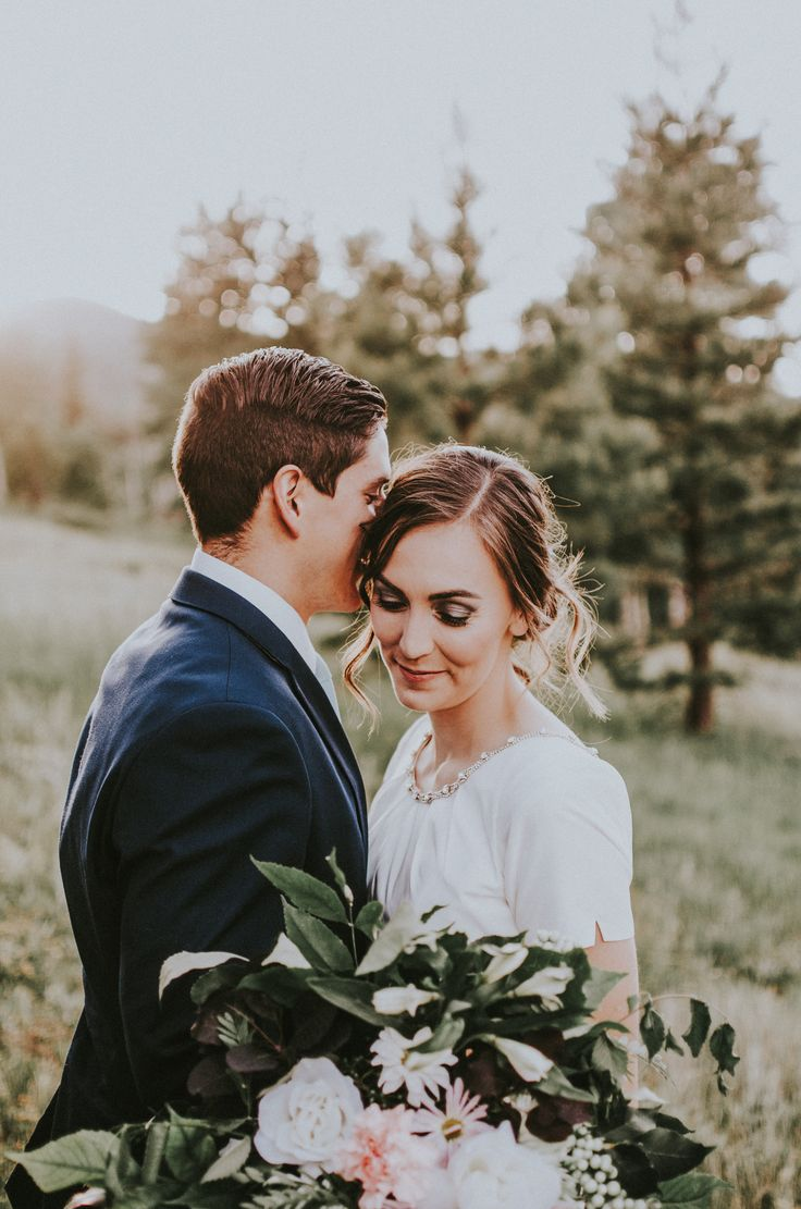 Close up and intimate wedding photograph of a sun kissed mountain elopement surrounded by pines. Photo by Simply Amor Photography