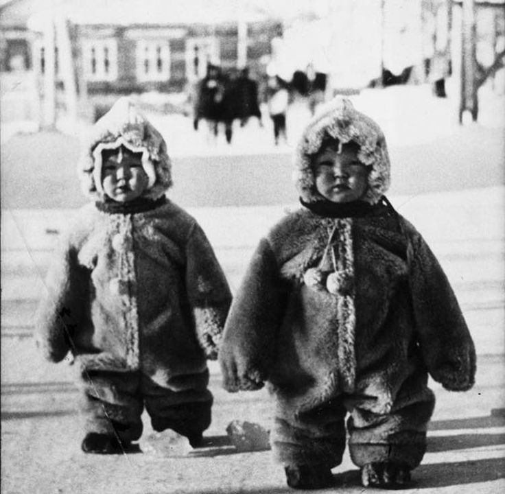 Twin toddlers in some Russian street are so well protected against cold so they look like penguins, 1968