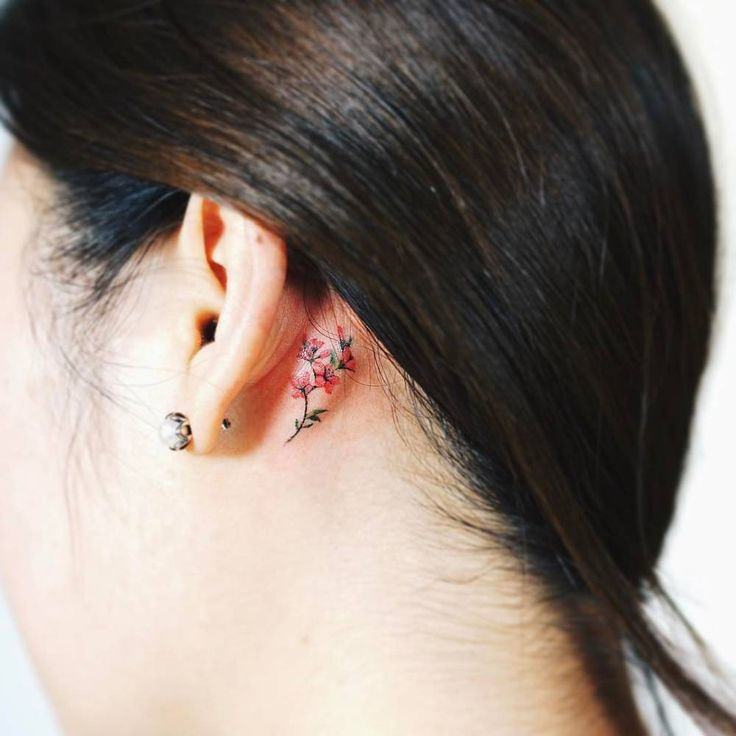 Tiny flower tattoo behind the left ear. Artista Tatuador: Nando