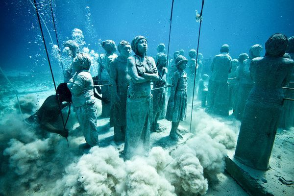 """""""Silent evolution"""" sculptures are lowered into the waters of Cancun in late 2010. Created by Jason Taylor and his team."""