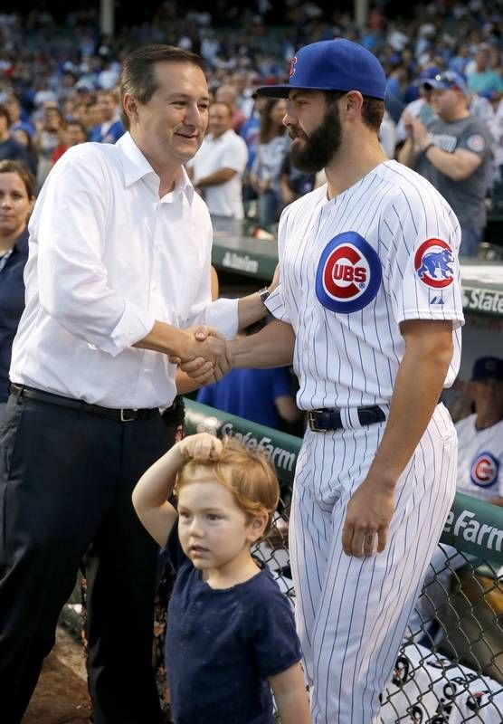 Chicago Cubs chairman Tom Ricketts congratulates pitcher Jake Arrieta as they watch a replay of his no-hitter against the Los Angeles Dodgers before Monday's game against the Cincinnati Reds.